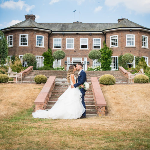 Couple kissing infront of Delamere Manor