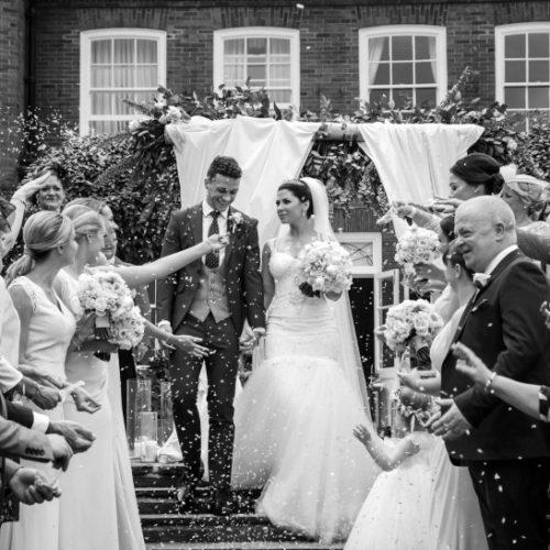 Couple walk through wedding confetti