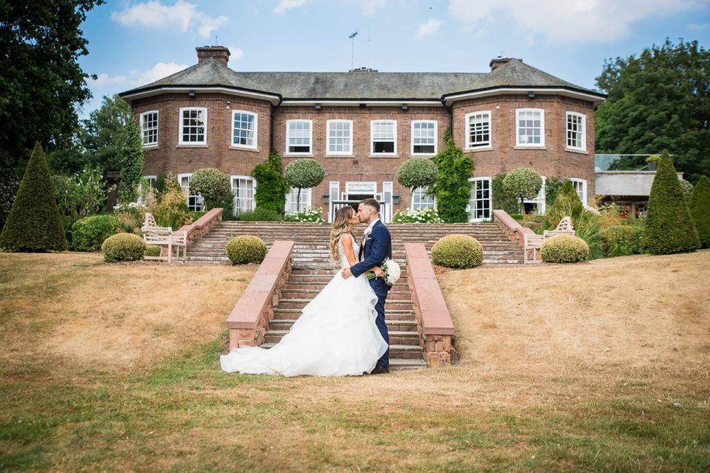Couple kissing outside Delamere Manor