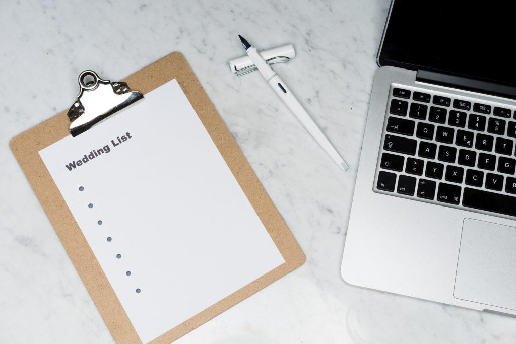 wedding checklist paper next to laptop