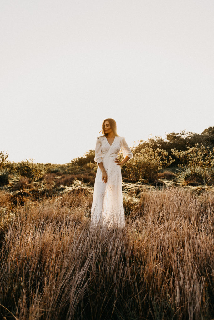 Image describes a woman in a white jumpsuit