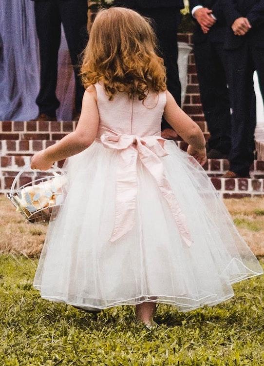 Image describes a flower girl at a wedding.