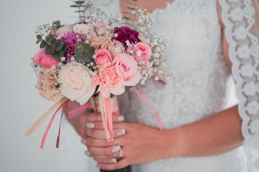 Image describes a bride holding a wedding bouquet.