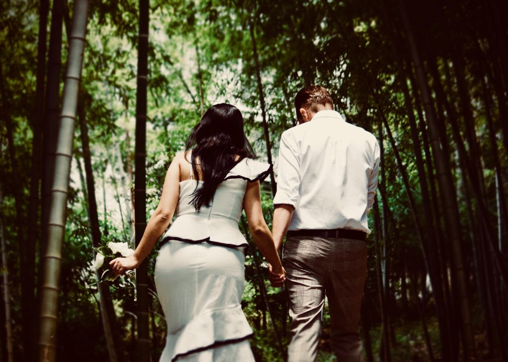 Image describes a wedding couple walking in the forest.